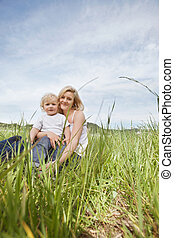 Mother sitting on grass with son