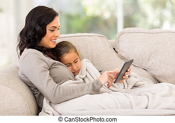mother sitting on the couch with her sleeping daughter