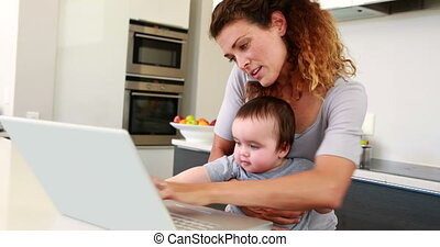 Mother sitting with baby boy on lap using laptop and talking...