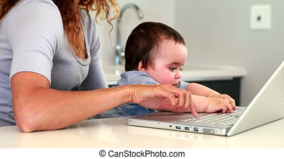 Mother sitting with baby on lap using the laptop at home in...