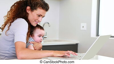 Mother sitting with baby on lap using laptop at home in the...