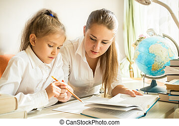 Mother sitting with daughter at desk and explaining task at...