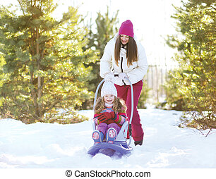 Mother sledding child in sunny winter day