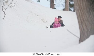 Mother sledding with child in the park