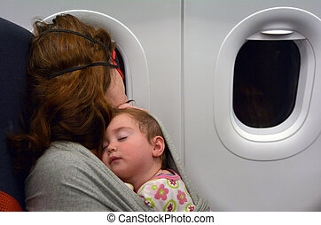 Mother sleep with her  baby during flight.