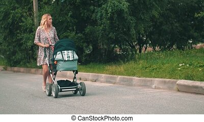 Mother slowly walking with baby carriage in green park. Summer day. Motherhood.
