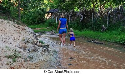 Mother Small Daughter Step from Sand Beach into Shallow Stream