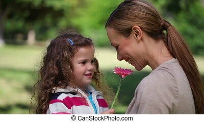 Mother smelling a flower holding by her daughter