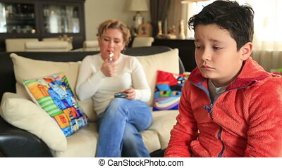 Mother smoking near her coughing child - Mother Sits On Sofa...