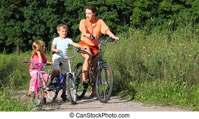 mother, son and daughter rides bicycles in park