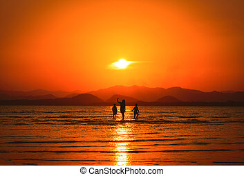 Mother, son and daughter silhouette on the beach at sunset.