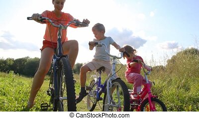 mother, son and daughter sits on bicycles in park