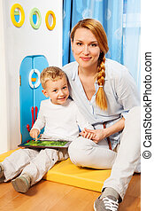 Mother son gadget - Mother and son sitting in bedroom and...