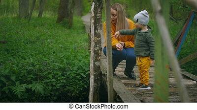 Mother spends time with her young son in nature telling and introducing him to nature and the surrounding world. Learn and explore the world together. Motherhood and childhood.