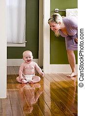 Mother standing beside happy baby sitting on floor