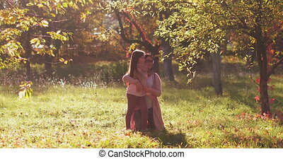 Mother standing on knees hugging daughter telling how much love her at the the autumn park among the trees with a colorful fairytale color. Copy space. Concept family. Tinted footage. Prores 422