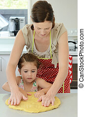 Mother stretches dough with her child