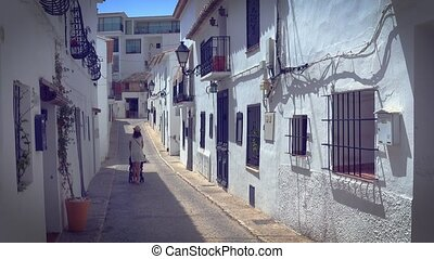 Mother strolling with newborn in a narrow street with white...