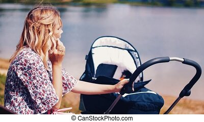 Mother sway baby carriage and speaking on phone in summer park at lake. Sunny.