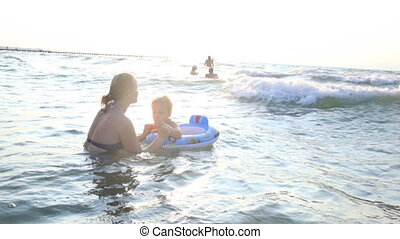 Mother swimming with her little boy in the sea