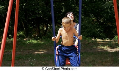 Happy Child Boy and his Mother Swinging on a Street Counterweight Swing at Playground. Slow Motion in 96 fps. Couple of young mother and little son 8 years having fun together in a street children's town. Leverage swing. Summer, sunny day.