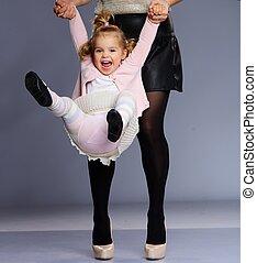 Mother swinging her happy little daughter