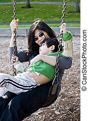 Mother swinging with her disabled son with cerebral palsy