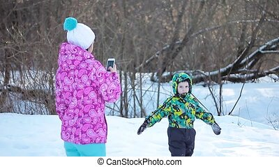 Mother Takes A Photo Of Her Son in winter forest