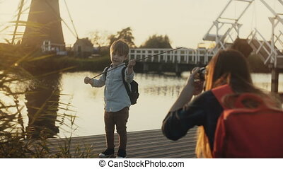 Mother takes photos of a boy child playing pirate. Family...