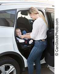 Mother taking her baby in safety seat out of the car