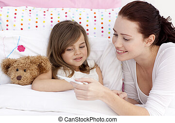 Mother taking her daughter\'s temperature