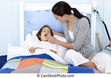 Mother taking her son\'s temperature with a thermometer