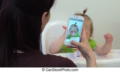 mother taking photo and video of baby using smartphone enjoying photographing cute toddler sharing motherhood lifestyle on social media. The girl eats for the first time