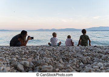 Mother taking photos of her kids on the beach