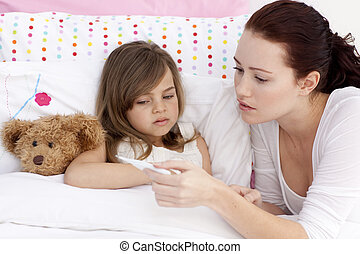 Mother taking sick daughter\'s temperature in bed