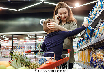 Mother talking on smartphone in supermarket