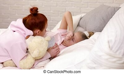 mother talking to child daughter in bed in the morning