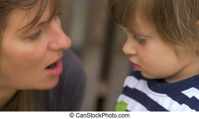 Mother talking to her young daughter mentoring and teaching...