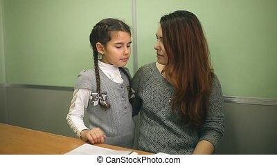mother talking with her daughter schoolgirl girl in school classroom