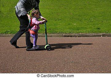 Mother teach her child to ride a scooter