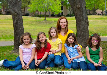 Mother teacher with daughter pupils in playground park