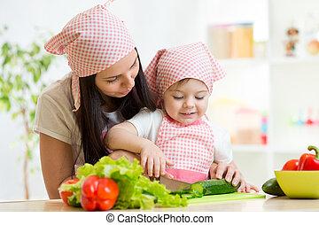 Mother teaches daughter knife cut cucumber - cute mother...