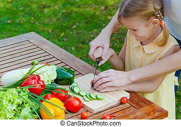 mother teaches daughter  knife cut cucumber