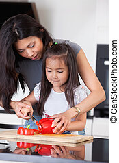 Mother teaches daughter to cook - Little girl cutting pepper...