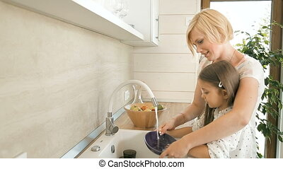 Mother Teaches Daughter to Wash Dishes
