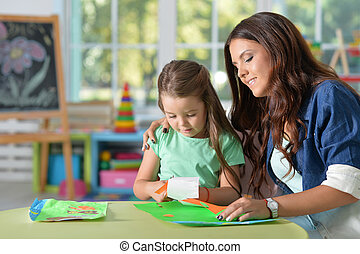 Mother teaches her cute little daughter to do craft items