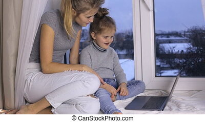 Mother teaches her daughter how to use laptop