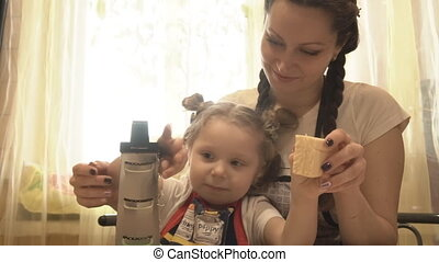 Mother teaches her daughter to use the peeler. They RUB the cheese