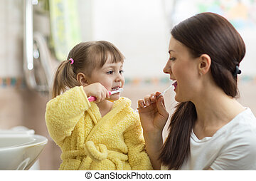 Mother teaches her little daughter teeth brushing