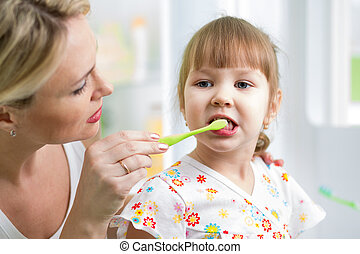 mother teaches kid teeth brushing